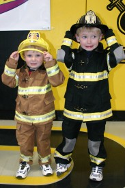 Kids dressing up in fire equipment.